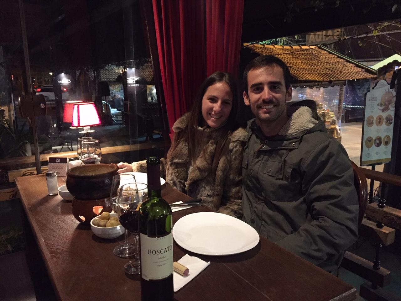 Miren y yo cenando fondue de queso acompañado de vino de la Serra Gaucha, una de las cosas que hacer en Gramado